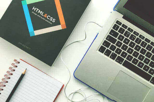 A laptop sitting next to a book about HTML and CSS web design