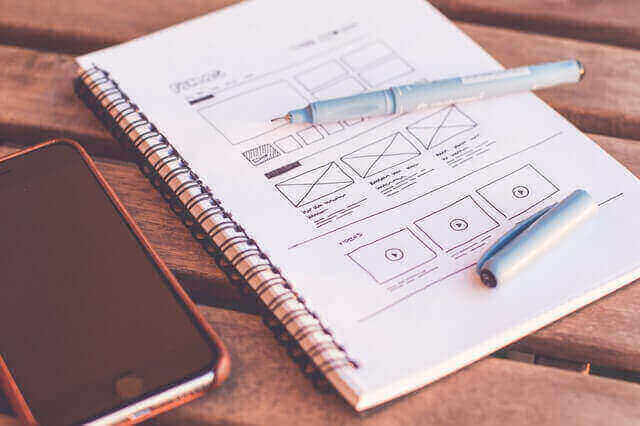 A notebook with a website layout sketched on its page sitting next to a phone and pen on a wooden table.